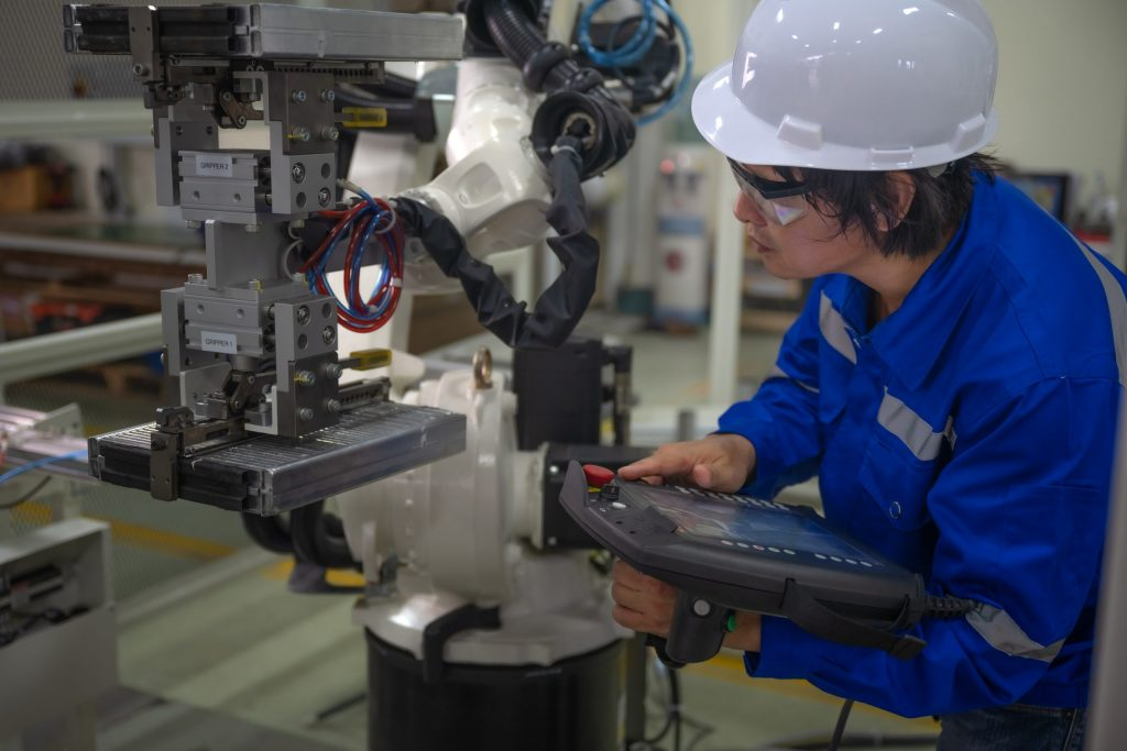 Technician inspecting a new system of robotic arms for industrial automation