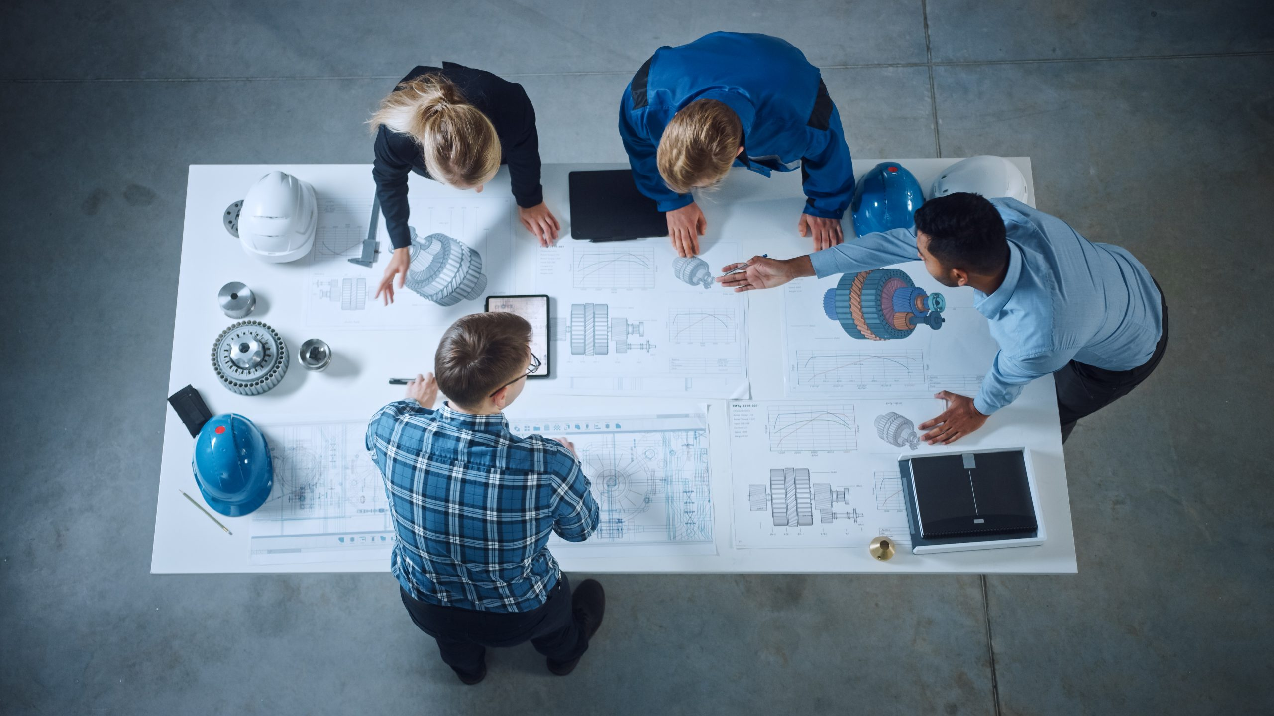 Team of Engineers Lean Over Table, Analyze Machinery Blueprints, Consult Project on Tablet Computer