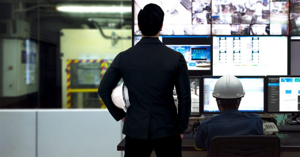 Engineers watch process control display on a wall of monitors.