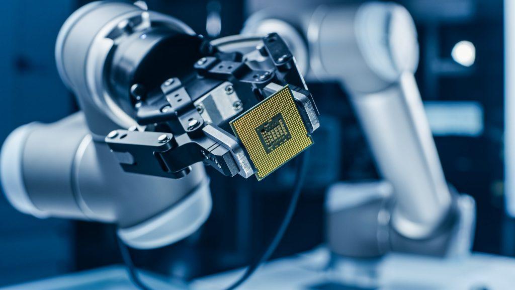 Robotic arm holding a supercomputer processor.