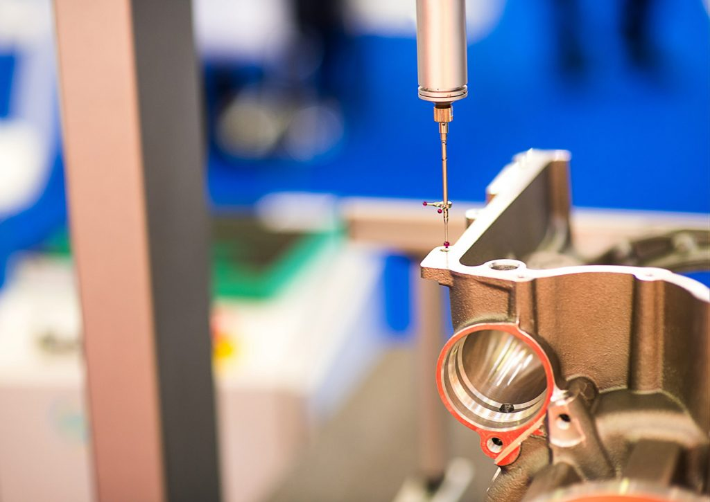 Coordinate Measuring Machine (CMM) probe measuring a machined part.