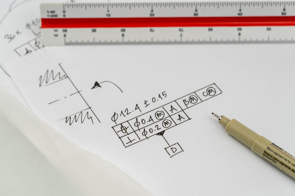 Hole positioning and dimensioning with geometrical tolerance. High resolution. Focus on pen tip.